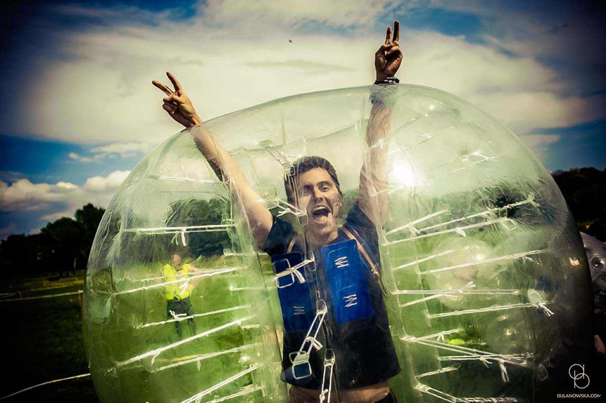 Person happy about taking part in the group bubble football activity in Warsaw