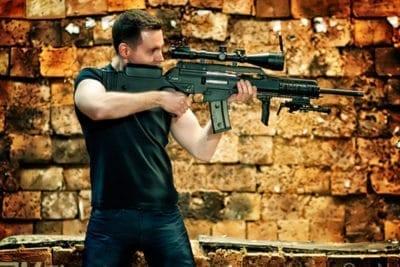 Människan går med en pistol för en pistolskytteaktivitet i krigssken