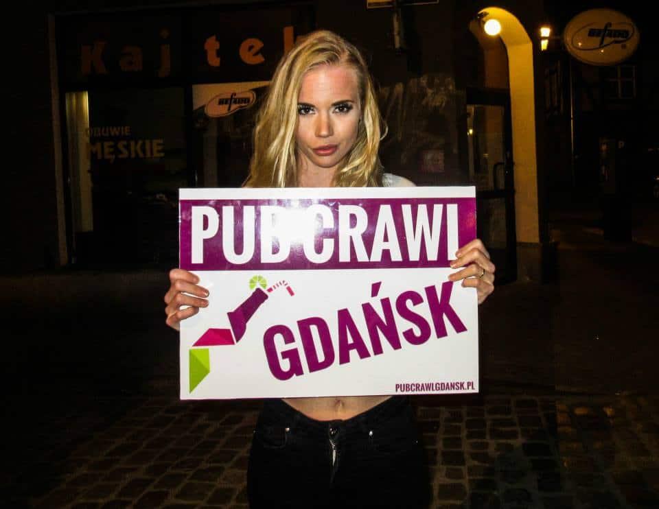 Girl with a Pub Crawl Gdansk signboard