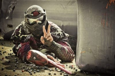 Guy in a mask showing a peace sign during the outdoor paintball activity in Gdansk